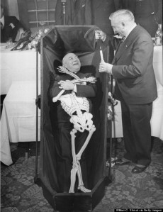 A man laying in a coffin with a paper sk
